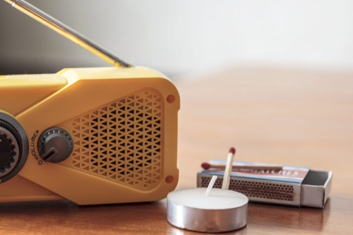 Storm supplies. Wind up weather radio with candle and matches.