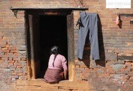 Frau vor ihrem Haus in Kathmandu