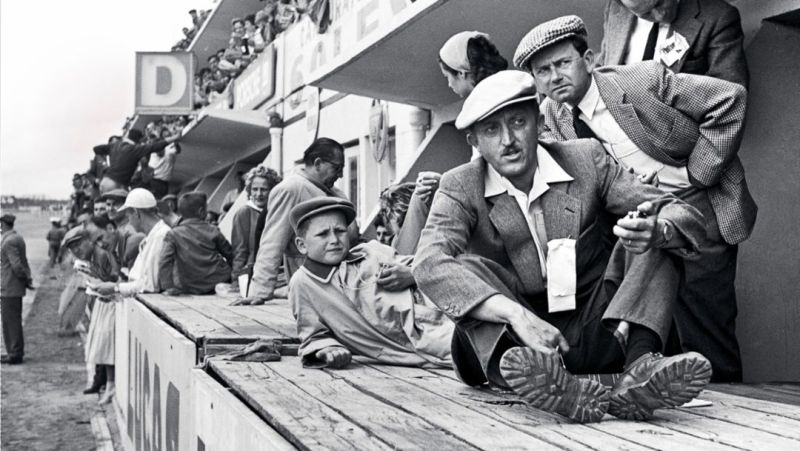 Wolfgang Porsche (1956, laying) with his father Ferry Porsche (plaid cap) and Hans Klauser (light cap) at the pit of the 24-hour race in Le Mans