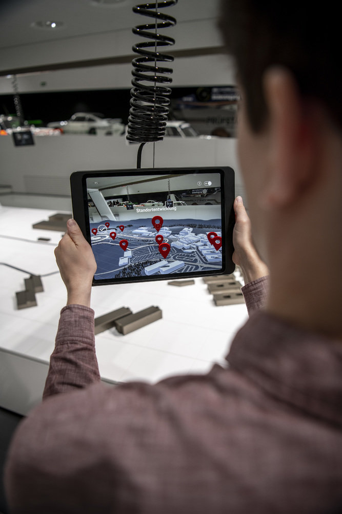 Using iPads and AR software, visitors can get to know the model of the Weissach site positioned at the center of the special exhibition.