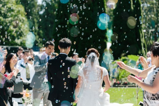 Back shot of bride and groom walking the asile while bubbles in the air