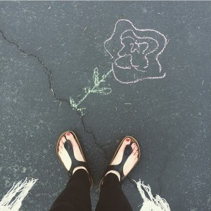 A photo of a rose drawn in chalk on concrete coming from a crack. This represents how love blooms from online couples therapy and marriage counseling in California. Contact an online therapist in California for support today!