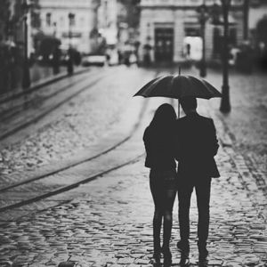 A couple share an umbrella in the street. Online couples therapy and marriage counseling in California can help relationships improve, and an online therapist can help make that happen! Contact a Sacramento therapist for support!