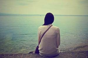 A woman sits alone as she looks out over a vast lake. This could represent isolation. Contact a Sacramento therapist to learn more about online grief counseling in California. A grief counselor would be honored to help you via online therapy.