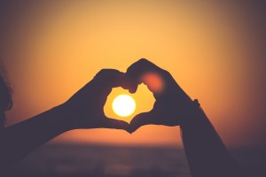 Two hands make the shape of a heart with the sun in the middle. This could represent the power of love. Contact a Sacramento therapist for online couples sex therapy, online couples therapy and marriage counseling, and more!