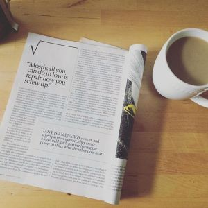A magazine rests next to a coffee mug for Love Heal Grow. Contact an online therapist in california for info about online LGBT therapy in california, online anxiety therapy, and other services.