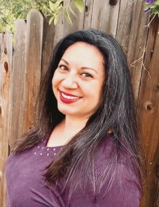 Veronica smiles for the camera in front of a fence. She is a Sacramento therapist offering online anxiety therapy in Sacramento, CA, online LGBT therapy, and other services.