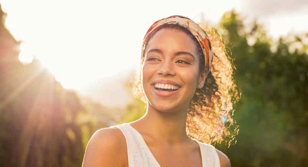 A young african american woman smiles brightly as the sun sets behind her. This could symbolize the joy and freedom that comes from overcoming anxiety. We offer anxiety treatment in Sacramento, CA, online anxiety therapy, and other services. Contact an anxiety therapist for more information.