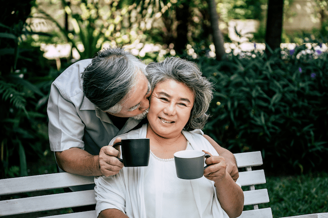 Older couple drinking coffee on a park bench. The man kisses the woman. This represents the joy that can be found in couples therapy sacramento and marriage counseling in Sacramento at Love Heal Grow