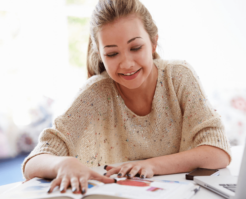 A smiling teen flips the pages of the textbook she is reading. This could represent a teen taking more joy from everyday activities after therapy for teens in Sacramento, CA. Contact a therapist for teens to learn if online therapy for teens in California could support you!