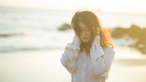 A woman holds her hair as the sea breeze flows by. An online therapist in California can provide sexual abuse therapy in sacramento, ca. Contact a therapist for sexual trauma for support today.