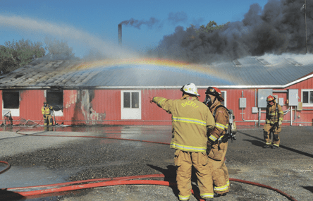 Spray from a water cannon creates a rainbow as firemen battle the fire that ultimately claimed the NEPECO shop and offices Sunday afternoon in Byron. Some 20 firemen fought the blaze for more than six hours. David Peck photo