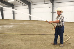 Fair board secretary Carl Nielson sprays down the new multi-pupose building floor at the Big Horn County Fairgrounds. Kynli Smith photo