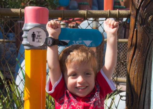 Child at Disneyland height requirement marker for Gadget Go Coaster