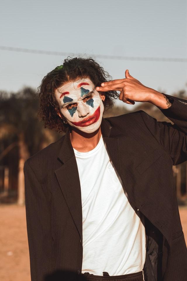 Man posing as joker pointing fingure gun at self