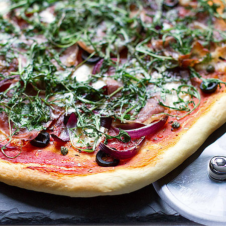 Parma ham, rocket, and red onion pizza