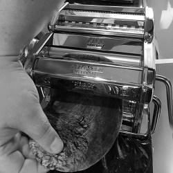 Cuttlefish Ink Fettuccine pasta dough being fed through pasta machine