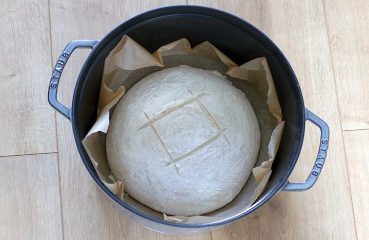 Scored sourdough loaf in Staub cocotte