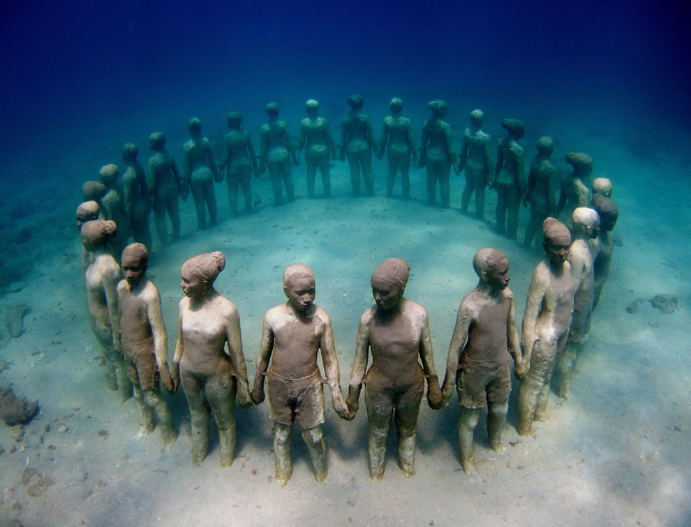 Vicissitudes, a ring of 26 standing children standing while holding hands and facing outwards