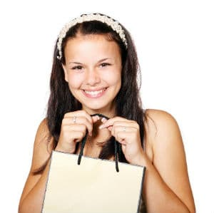 Young cute woman smiling with a shopping bag