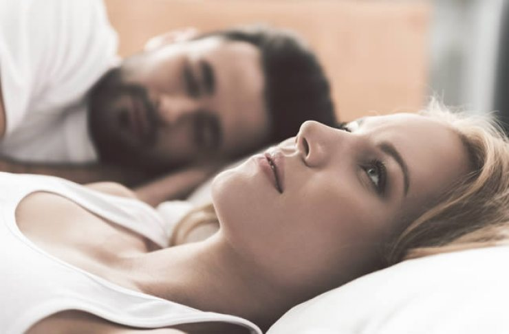 Worried lady lying awake in bed with partner sleeping