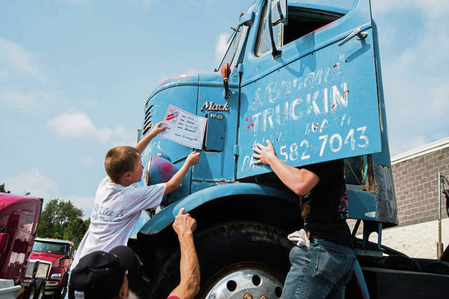 Easton Shermenti, 7, of Saltsburg, places a identification card on his family's antique 1985 Mack truck while his brother, Gavin Miller, 17, checks on the inside of the cab on Saturday, July 6, 2019 at the Steel Valley chapter of the American Truck Historical Society antique truck show at Kenworth of Pennsylvania in New Stanton.