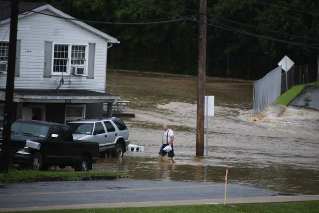 A resident of Brush Creek Road wades through flood waters on Thursday, July 11, 2019 in Manor.