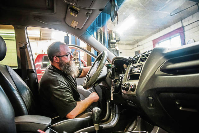 Shop Manager Dwayne Emerick, 42, performs a vehicle emissions test before beginning the safety inspection at Dwayne's Auto & Truck Service in South Greensburg on Friday, Jan. 24, 2020.