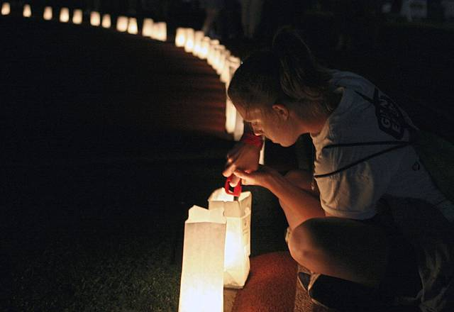 Area American Cancer Society Relay For Life teams will host a July 30 luminaria night at Westmoreland County Community College Youngwood campus. Here, Jackie Butler of North Huntingdon lights luminaria at the 2007 Relay at Norwin High School.