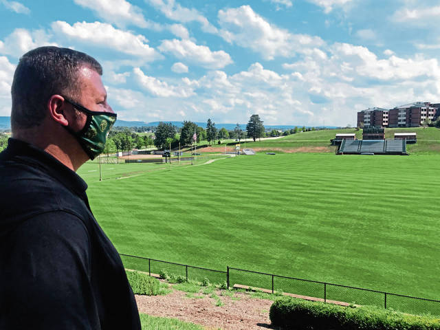 Jim Berger, associate director of marketing and communications at Saint Vincent College, looks over the green, but empty, expanse of Chuck Noll Field on Friday, July 24, 2020, on the college campus in Unity. A year earlier, the site was alive with players and fans during the annual Steelers summer training camp. The 2020 camp was canceled in accordance with NFL health precautions during the covid-19 pandemic.