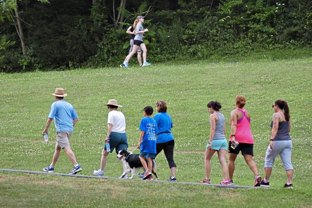 Runners and walkers climb the hill out of Lynch Field in Greensburg at the start of the annual Five Star Trail Poker Run.