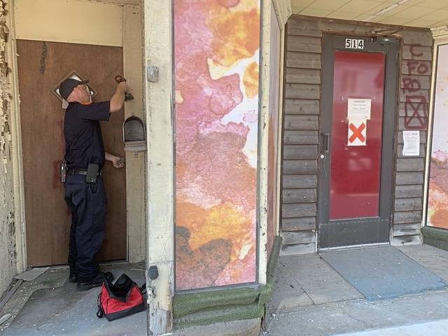 Jeannette Fire Chief Bill Frye secures a door of an abandoned building on Clay Avenue on Wednesday. Frye has been marking blighted buildings that are potentially dangerous to first responders and to create an inventory of dilapidated structures in the city.