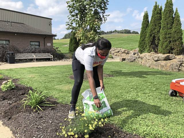 Seton Hill University senior Taylin Tyler of East Liberty, spreads fertilizer Saturday on flowers planted at Hempfield Park <ins>,</ins> <ins>Sept. 12, 2020,</ins> as part of the university's Labor of Love, Saturday of Service.