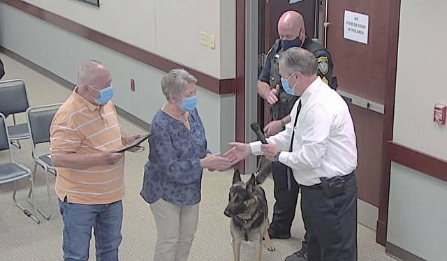 Murrysville Police Chief Tom Seefeld presents George and Maxine Thomas of Murrysville with a plaque, recognizing the couple's donation to fund the purchase and training of a new K-9 officer, Magnus, seen here with handler Sgt. Scott Kettren.