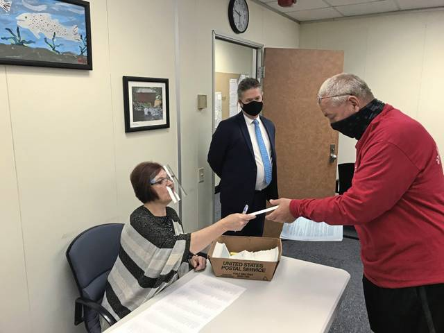 Kevin Powanda (right), owner of 4 Seasons Travel in Irwin, is handed a $25,000 check on Wednesday from Treasurer's Office clerk Kimberly Sandzimier as Donald O'Brien, chief of staff to Commissioner Gina Cerilli, watches. County commissioners last week awarded 260 small businesses grants totaling $4.3 million to cover loses associated with the coronavirus pandemic. Grants will be handed out again at the courthouse on Thursday, Monday and by appointment.