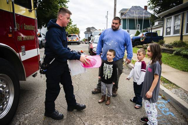 Brett Locke, 14, with Greensburg Fire Department, brings toy firefighter hats and bags of goodies for Aubrii Maybury, 9, right, her two younger brothers, Landon Maybury, 5, and Tommy Maybury, 4, left, as their dad Justin Maybury looks on Sunday in Greensburg. Locke and other members of Greensburg's fire departments paraded through town in fire trucks delivering handouts to kids for Fire Prevention Day.