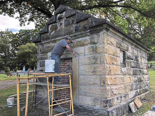Art Cochenour of Turkeytown, who owns a mansonry business, works on the stone facade of the Suter family mausoleum in the West Newton Cemetery.