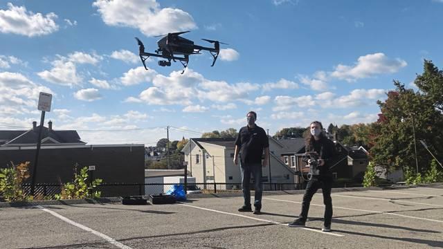 Indiana University of Pennsylvania student Spencer Samios (right) pilots a drone to photograph Greensburg's Buncher parking lot as professor John Benhart supervises Thursday.