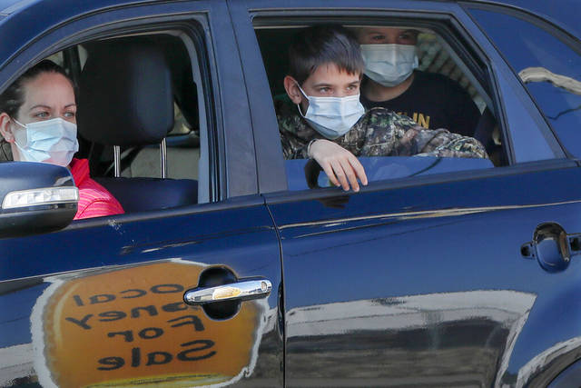Members of the Folman family from Murrysville, wear protective masks in their car as they look at a table with honey for sale at the Greensburg Farmers' Market opening day, Saturday, April 25, 2020, in Greensburg.
