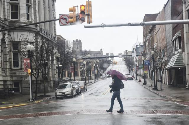 A person carrying an umbrella crosses S. Main Street in Downtown Greensburg on Friday, Jan. 1, 2021.