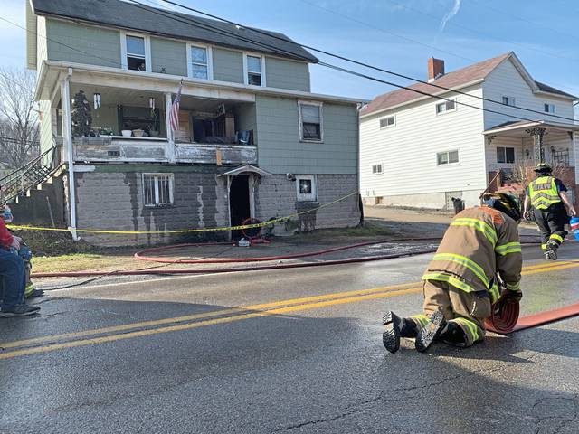 A firefighter rolls up a fire hose on Huntingdon Street in Yukon after crews extinguished a basement fire at a home on Thursday, Jan. 14, 2021.