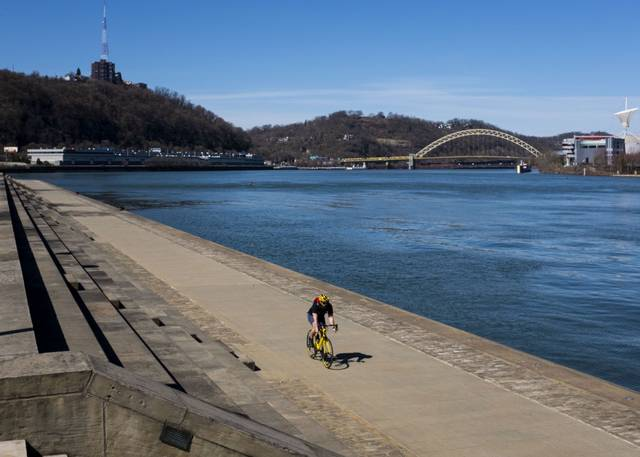 A cyclist rides along the Allegheny River in Downtown Pittsburgh on March 30.
