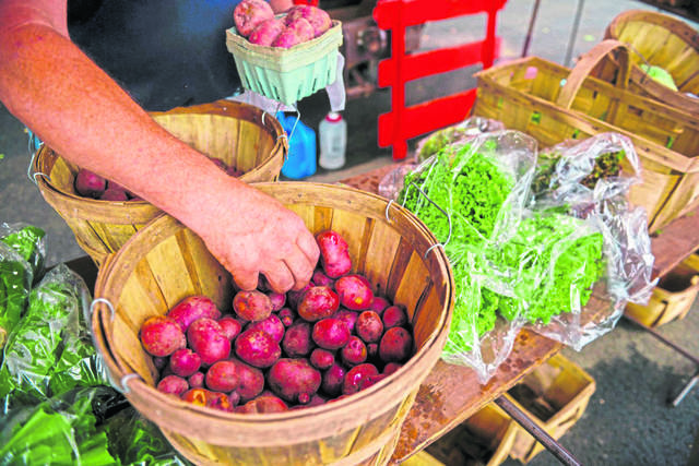 Paul Sarver of Sarver Hill Organic Farm selects red potatoes for a customer during a 2018 Greensburg Farmers Market at Lynch Field.
