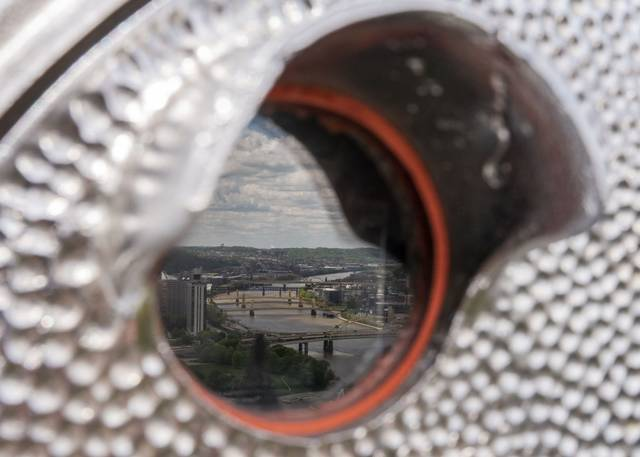 Bridges spanning the Allegheny River are seen in the reflection of a coin operated binocular machine next to the Duquesne Incline on May 11.