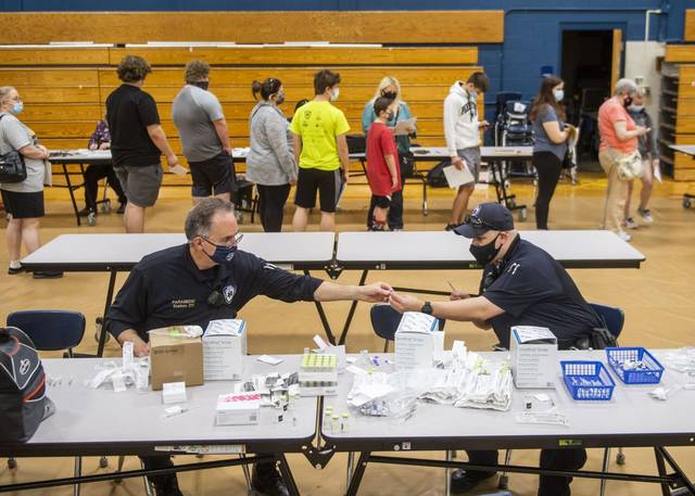 North Huntington EMS paramedics organize needles with covid-19 vaccines at a clinic at Norwin High School last month.