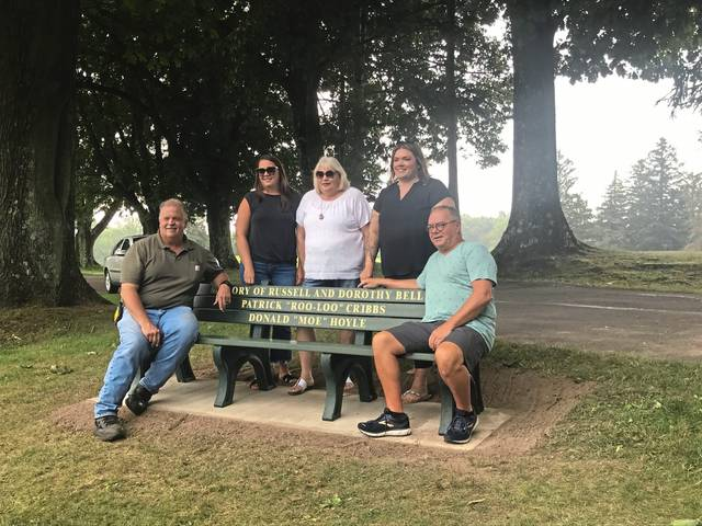 From left, Tom Bell, Michele Cribbs, Deborah Cribbs, Nicole Cribbs and Rick Hoyle pose with a new memorial bench at Mt. Odin Golf Course in Greensburg.
