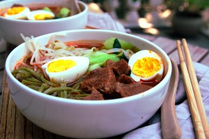 A bowl of chinese beef kelp noodle soup with beef cubes. soy bean sprouts and a boiled egg. Served with spoon and chopsticks