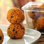 Two carrot coconut balls atop each other on a plate, with a glass jar full of more balls in the background