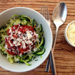A white bowl of zucchini pasta with sauce bolognese and parmesan cheese