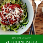 A white bowl with zucchini pasta with sauce bolognese and parmesan, served with fork and spoon on a wooden board